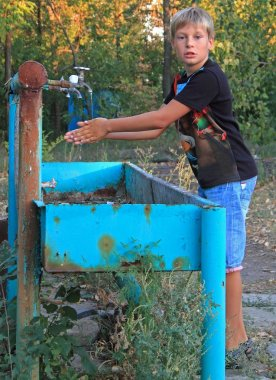 boy is washing hands in outdoor wash basin