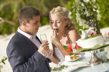 Lovely couple eating wedding cake during tropical marriage cerem