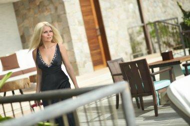 Beautiful, sexual girl walking on terrace with luggage bag.