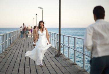 Gorgeous wedding couple walking through pier, splashes and drops