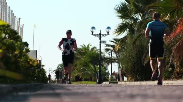 Szocsi, Oroszország - 1 szeptember 2020: Háttér elmosódott futó emberek másolja a helyet. Maraton, egy csomó ember fut. Lassú mozgás. Összpontosítás nélkül. Homályos. lábfutók