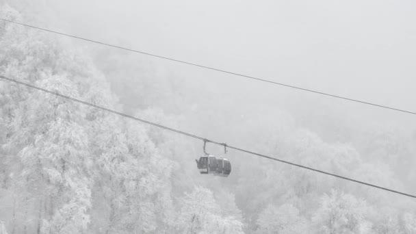 Winterpanorama mit Skiliften und schneebedeckten Bergen. Zweierseilbahn auf einer Skipiste im winterlich verschneiten Wald.
