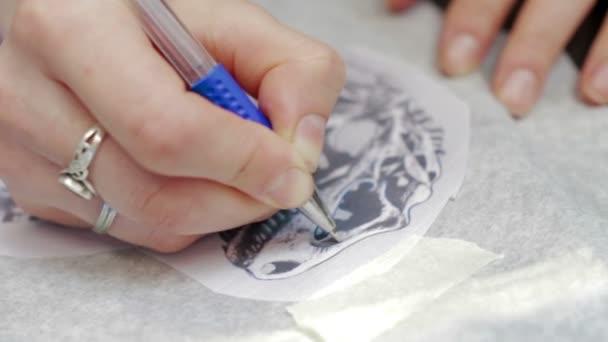 Female tattoo artist drawing Dinosaur sketch
