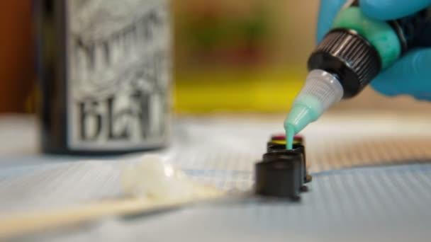 tetováló művész előkészíti a festéket a munka