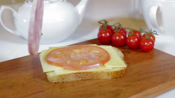 Making sandwich with tomato, ham and cheese