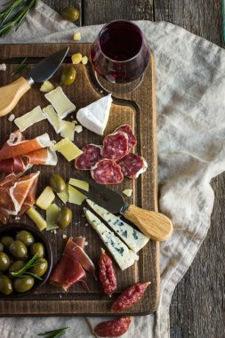 Assortment of various types of cheese and meat on wooden board