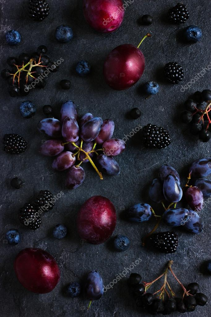 fresh dark fruits and berries on black background.