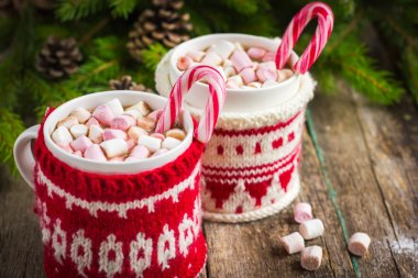 Mugs with hot chocolate and murshmallow and candy cane, wrapped