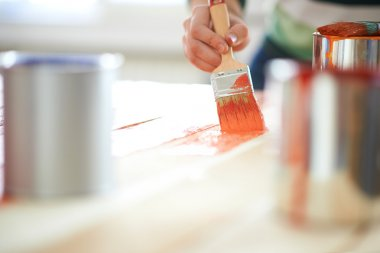 Woman painting furniture with paint brush