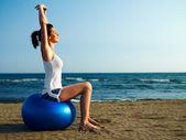 Donna che fa pilates sulla spiaggia