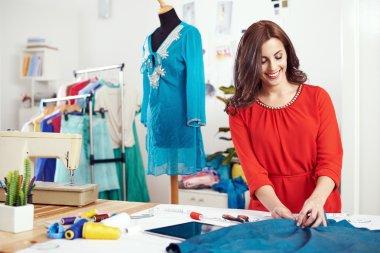 female designer measuring material