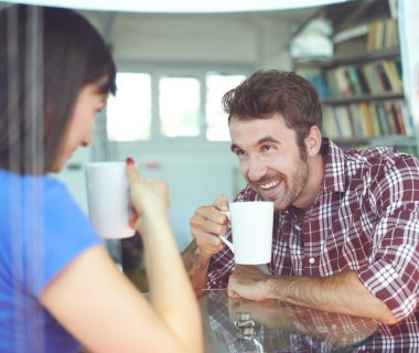 couple sitting inside apartment and drinking coffee