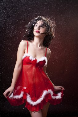Sexy Santa helper woman in red dress with feathers. Snowing