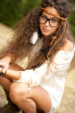 Beautiful hippie girl with glasses in the park