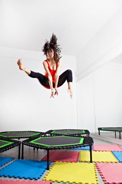 Jumping brunette woman on a trampoline. Wearing red top