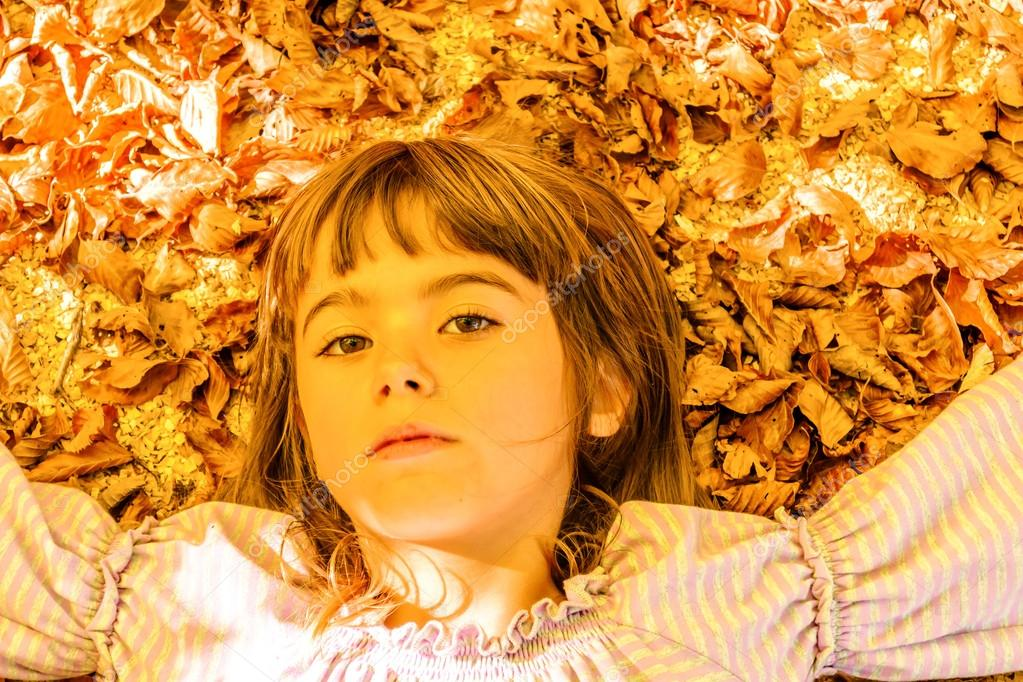 Little girl laying on the bed of leaves