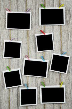 empty black photo frames hanging with clothespins on wooden back