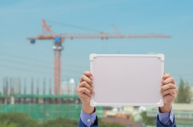 business man hand holding white board with construction site background