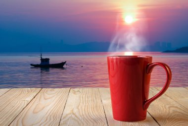 Red coffee cup with smoke on sun rise background