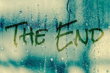 Natural water drops on glass window with the text The end