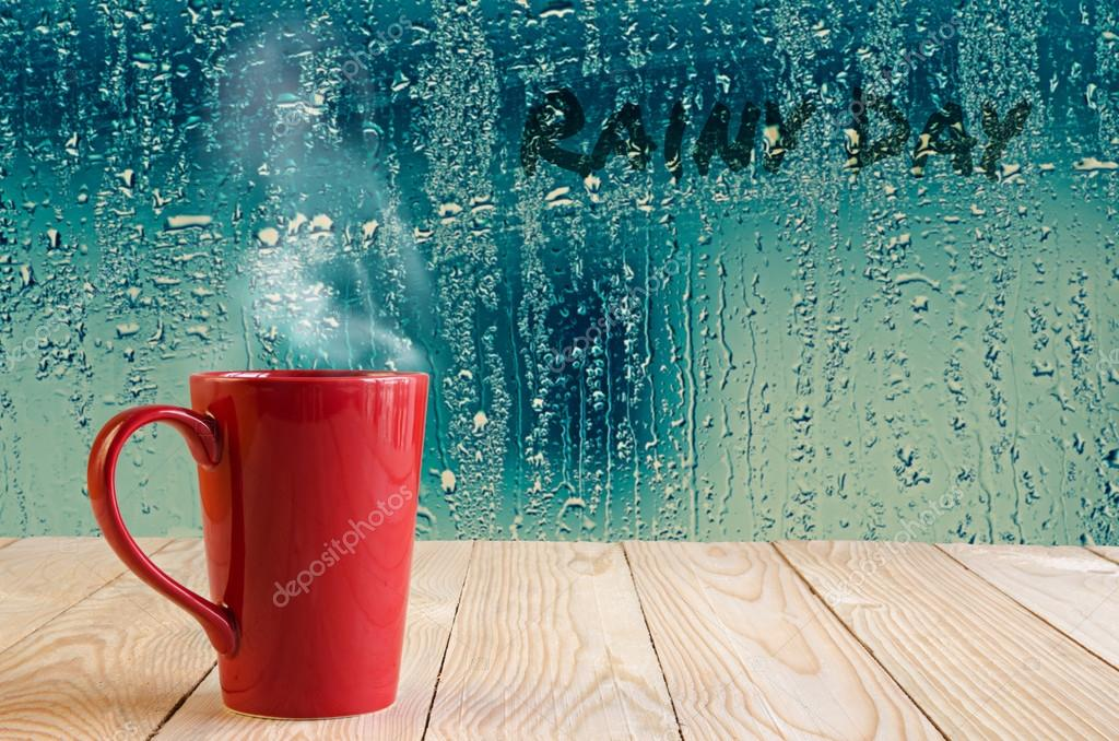 red coffee cup with smoke  on water drops glass window backgroun