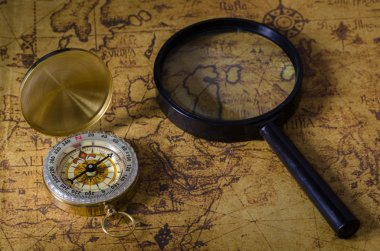 Compass and magnifying glass on old map