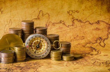 Compass and stack of coins on old map