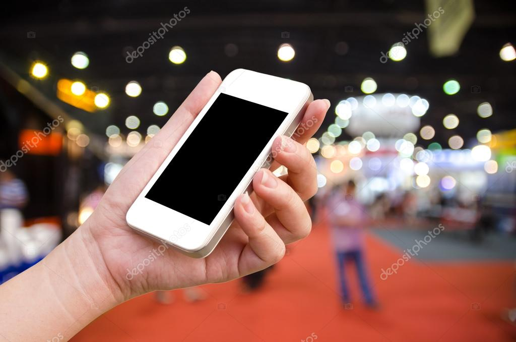 woman hand holding the phone tablet on blur event background