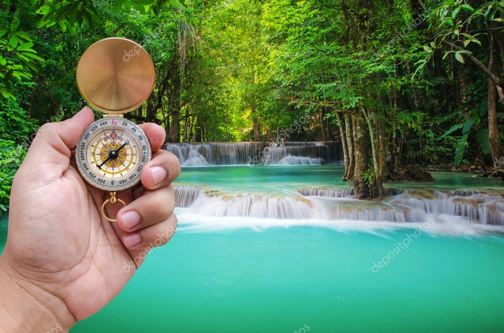 Man hand and compass with beautiful deep forest waterfall backgr