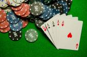 Playing cards Four of a kind and chips on green background