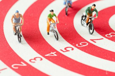 Miniature people cycling on darts