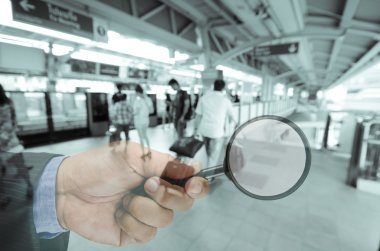 business man hand holding magnifier searching something , busine