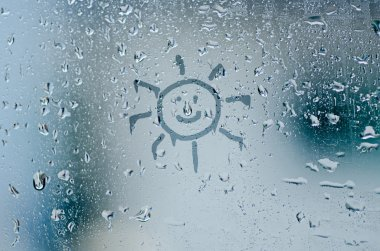 sun sign on natural water drops on glass window background