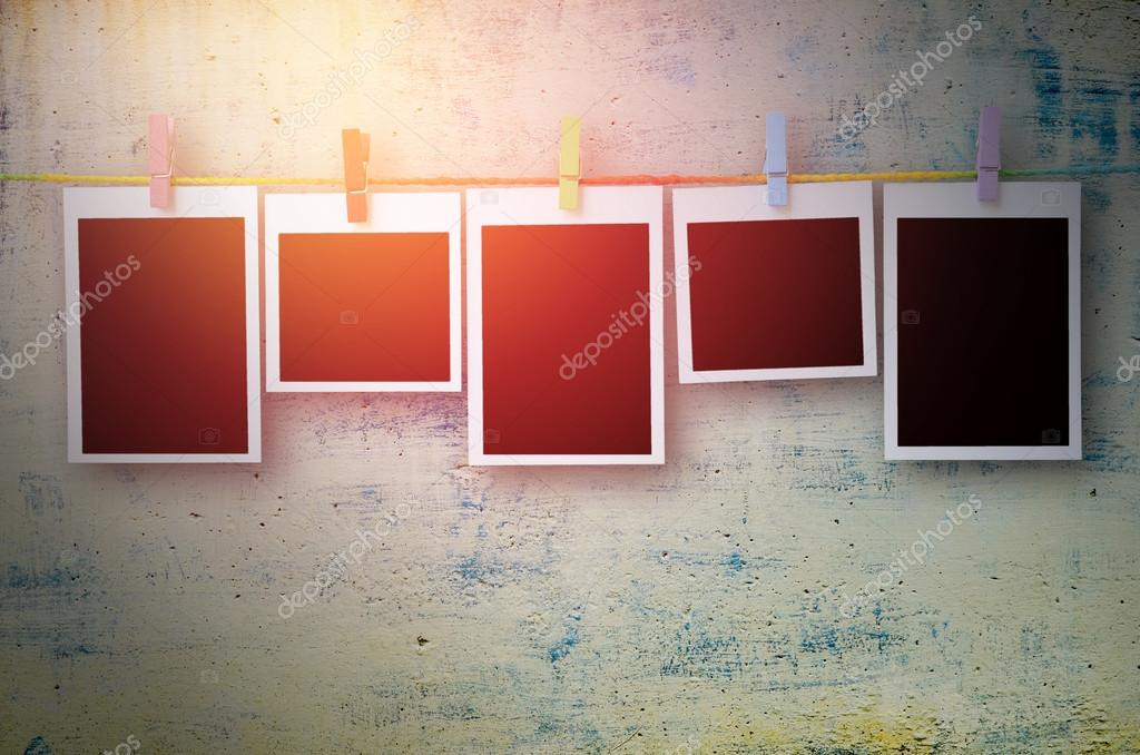 empty black photo frames hanging with clothespins on stone wall