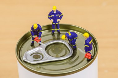 Miniature workmen team trying to open food can lid