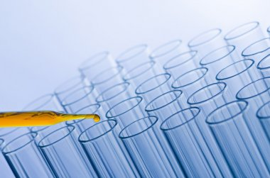 science laboratory pipette with drop on test tube background , l