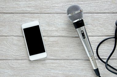 microphone and smart phone on white wooden table