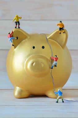 Miniature climbers climbing on gold piggy bank