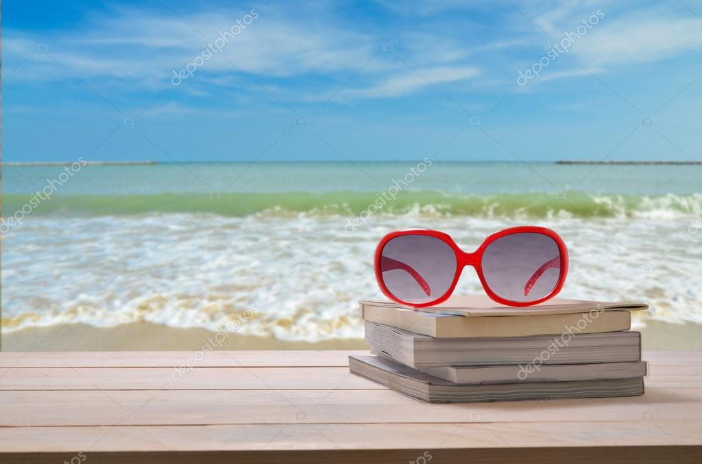 red sun glasses on stack of book with seascape backgroud