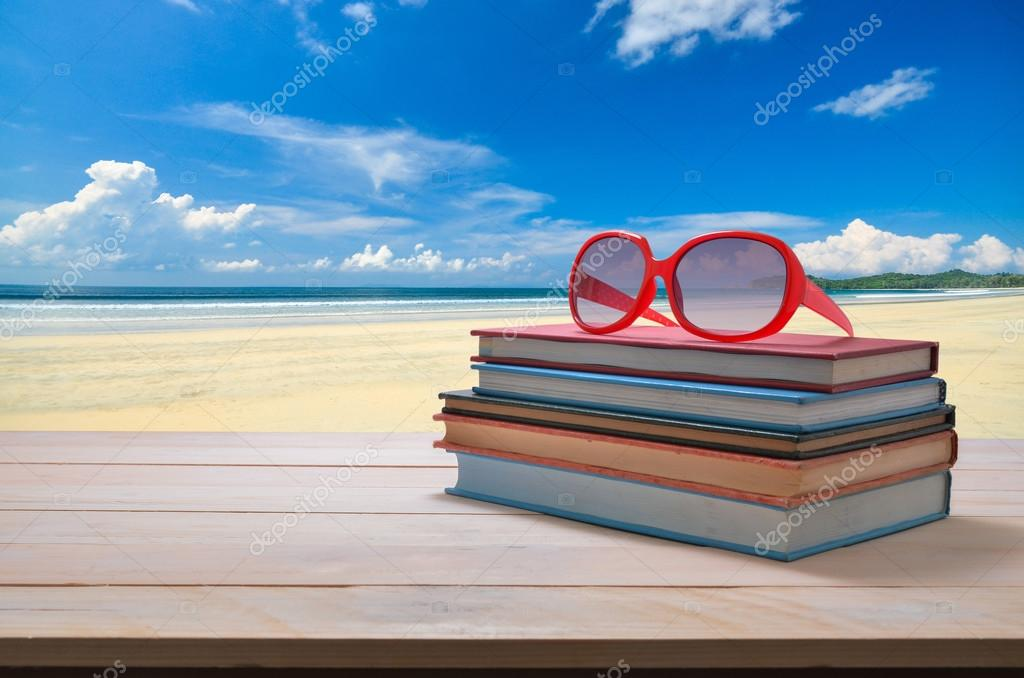 red sun glasses on stack of book with seascape background