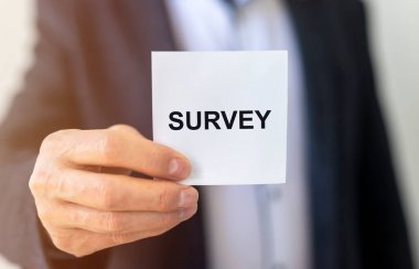The word Survey on paper in male hand. Poll or census concept.