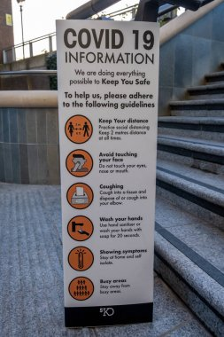 London, UK - November 2, 2020: A sign with COVID- 19 information to remind visitors to follow social distancing, wear a mask when necessary and regularly wash their hands
