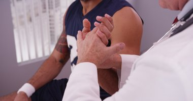 Male caucasian doctor checking wrist of male african sports athl