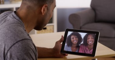 Black friends video chatting on tablet