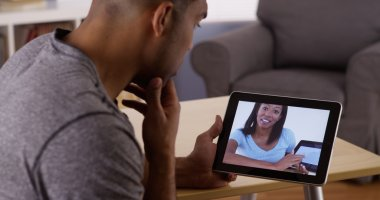 Black man talking with business colleague on tablet