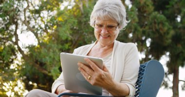 Senior woman happily surfing the web on tablet at the park