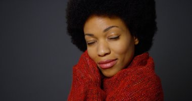 Black woman with afro wearing red shawl