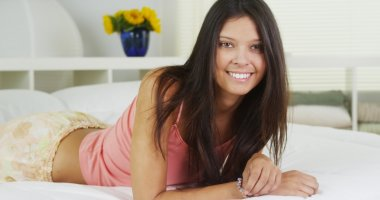 Cute Hispanic woman lying in bed smiling