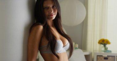 Hispanic woman standing in bedroom in lingerie