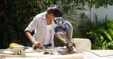 Black woman doing home improvement measuring wood
